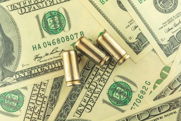 Bala para uma arma na mesa com notas de dólar americano, fundo de conceito de criminoso e máfia