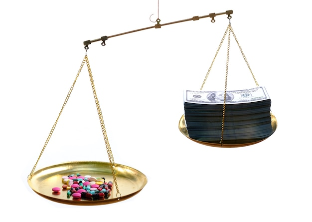 Balança com remédio de um lado e nota de 100 usd do outro na superfície branca, conceito de tratamento caro