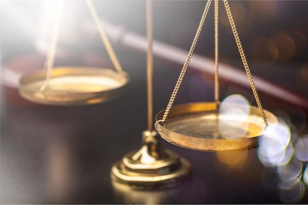 Balança da justiça e martelo de madeira na mesa de madeira
