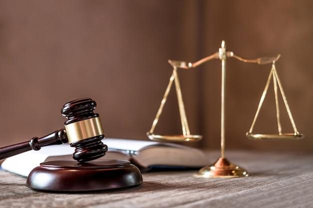 Balança da justiça e martelo na mesa de madeira e acordo na sala de audiências