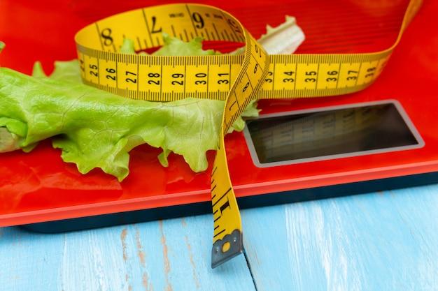 Balança eletrônica digital com fita métrica, alface. dieta, conceito de emagrecimento.