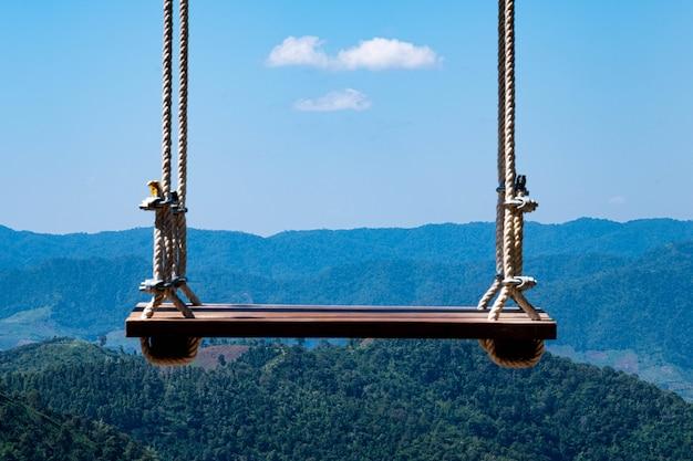 Balançar em uma varanda alta atrás das montanhas e céu claro há nuvens flutuantes na paisagem inspiradora. conceito de sonho