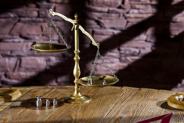 Balanças antigas em cima da mesa na parede de fundo com sombras