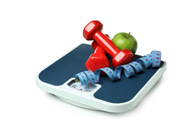 Balanças com halteres, maçã e fita métrica isoladas em branco