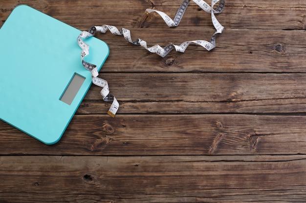 Balanças de chão azul e fita no fundo escuro de madeira