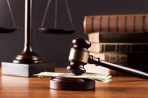 Balanças de justiça, livros e martelo de madeira com dinheiro na mesa. conceito de justiça