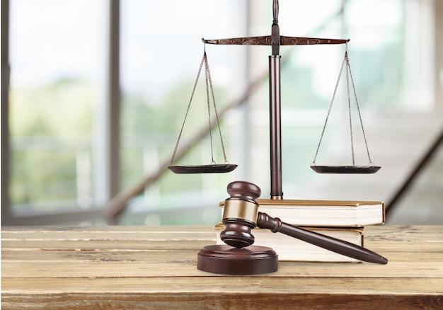 Balanças de justiça, livros e martelo de madeira na mesa. conceito de justiça