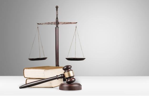 Balanças de justiça, martelo e livros sobre fundo claro