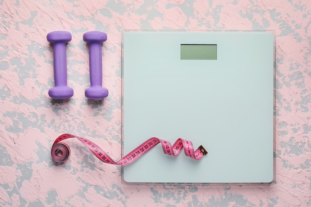 Balanças de peso com fita métrica e halteres. conceito de emagrecimento