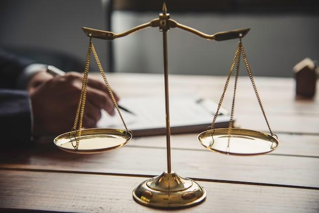 Balanças de tribunal na mesa e empresário trabalhando em segundo plano