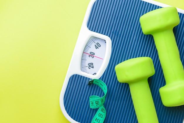 Balanças, halteres e fita métrica. conceito de perda de peso