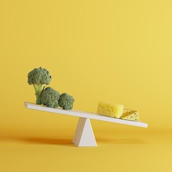Balancê de queijo que derruba com vegetais dos brócolis na extremidade oposta no fundo amarelo.