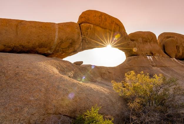 Balance o arco no por do sol no parque nacional de spitzkoppe na namíbia.
