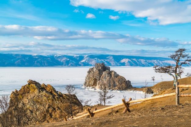 Balance shamanka e a árvore santamente no cabo burkhan na ilha de olkhon no lago baikal congelado, rússia.