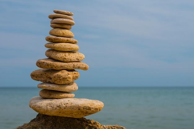 Balanceamento de pirâmide de pedras em uma grande pedra à beira-mar