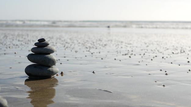Balanceamento de rocha na praia do oceano, empilhamento de pedras pelas ondas da água do mar. pirâmide de seixos na costa arenosa. pilha estável ou pilha em foco suave com bokeh, close-up. cinemagraph em loop sem costura. equilíbrio zen.
