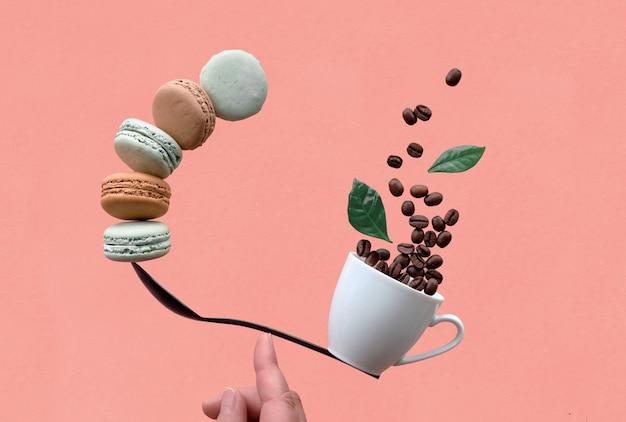 Balanceamento de xícara de café e macarons em uma colher na parede de coral