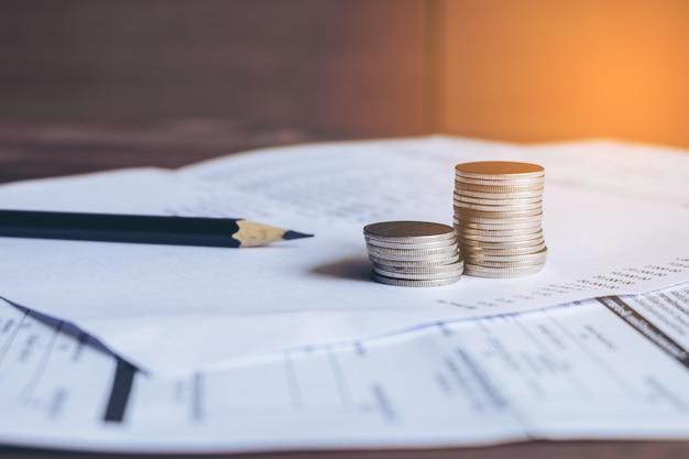 Balanço com lápis e moedas no extrato bancário, conceito da conta.