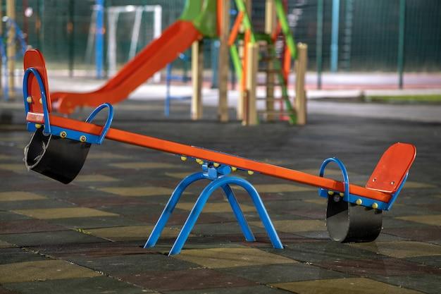 Balanço de gangorra no pátio da pré-escola com piso de borracha macia à noite.