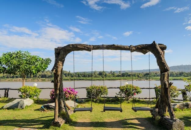 Balanço de jardim vintage de madeira na margem do rio