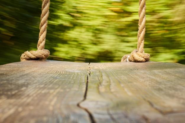 Balanço de madeira com cordas grossas. a câmera está no balanço