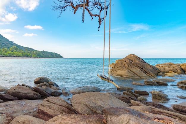 Balanço de madeira na bela pedra, praia e mar