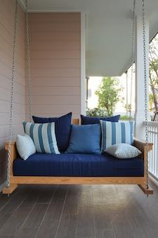 Balanço de madeira vintage com almofadas azuis em casa