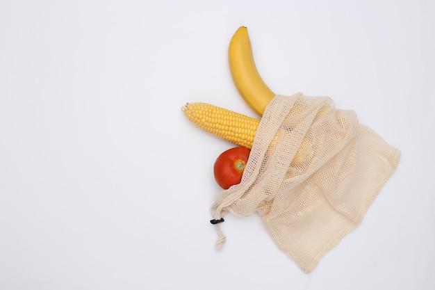 Balanço de milho, tomate e banana em saco de algodão eco em fundo branco.