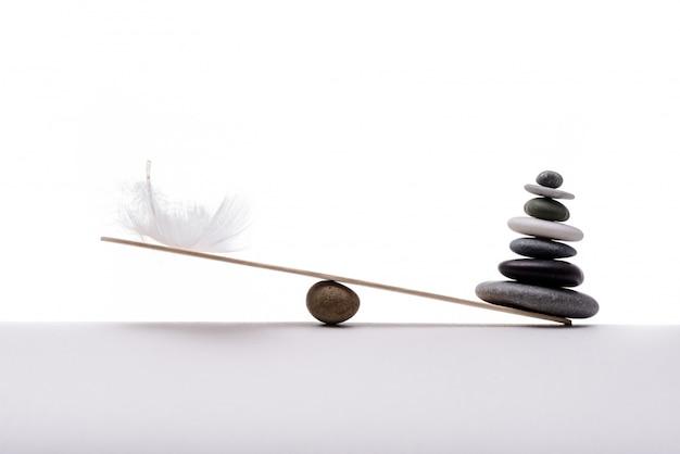 Balanço de pedra com pluma. conceito de pesado e leve.