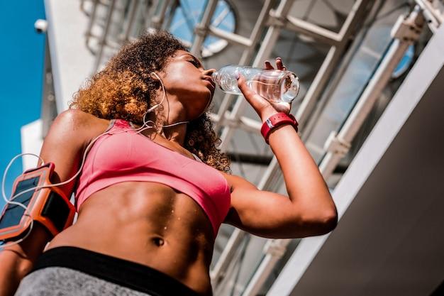 Balanço hídrico. ângulo baixo de uma bela jovem segurando uma garrafa enquanto bebe água