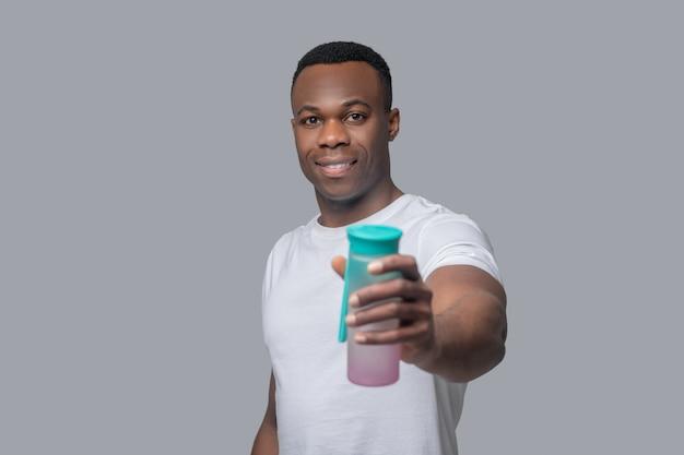 Balanço hídrico. um jovem de pele escura segurando uma garrafa com água