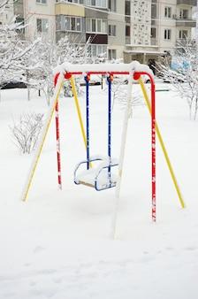 Balanço infantil, coberto com uma espessa camada de neve depois de uma forte nevasca