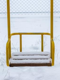 Balanço infantil coberto de neve no inverno sem crianças, horário de inverno