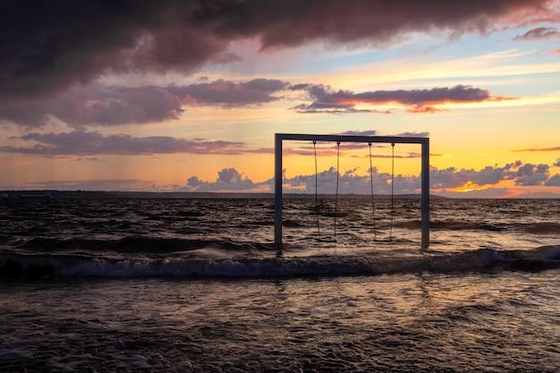 Balanço no pôr do sol do mar e praia, suécia, helsingborg