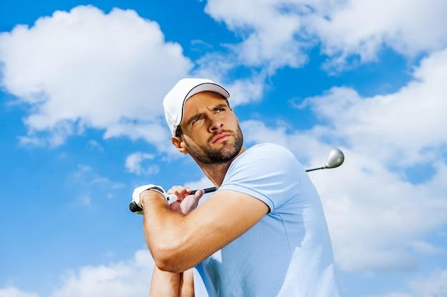 Balanço profissional. vista de baixo ângulo de um jogador de golfe jovem e confiante balançando seu driver e olhando para longe com o céu azul como pano de fundo