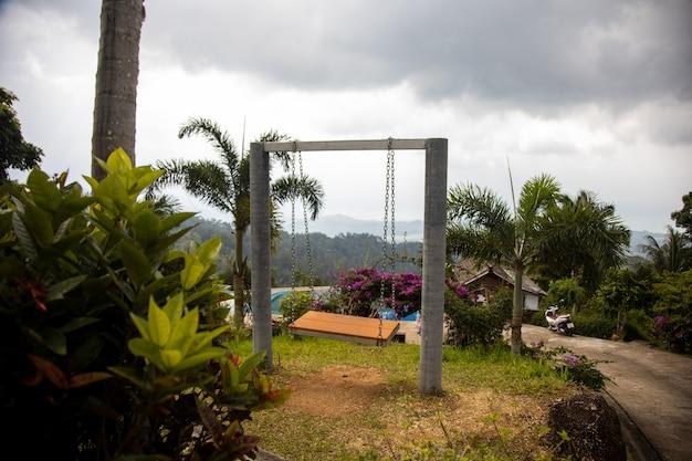 Balanço romântico vazio em um jardim paradisíaco tropical na encosta de uma montanha