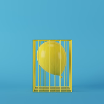 Balão amarelo conceito mínima flutuando na gaiola amarela sobre fundo azul