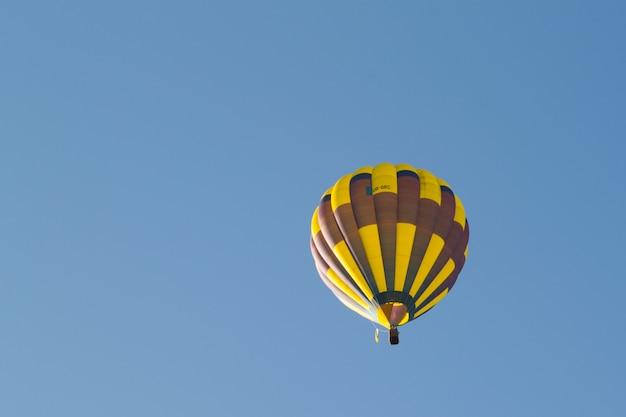 Balão amarelo contra um céu azul. aeróstato. pessoas na cesta. diversão. entretenimento de verão. aventuras românticas.