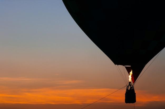 Balão colorido flutuando ao pôr do sol