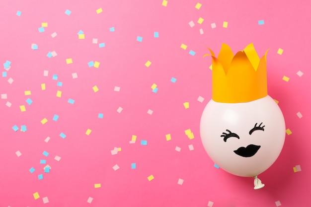 Balão com cara feliz no fundo rosa decorado, espaço para texto