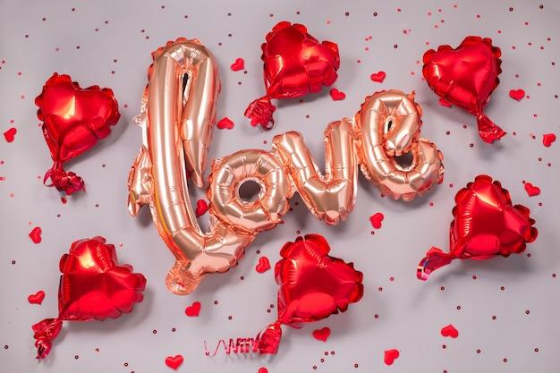 Balão de ar bege pastel na forma da palavra amor com pequenos corações vermelhos