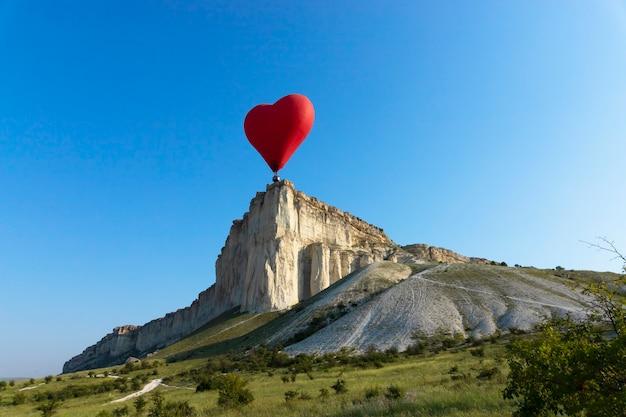 Balão de ar quente, balão vermelho em forma de um coração voador no contexto da pedra branca. foto de alta qualidade