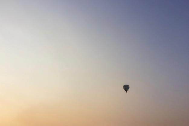 Balão de ar quente colorido com céu do por do sol.