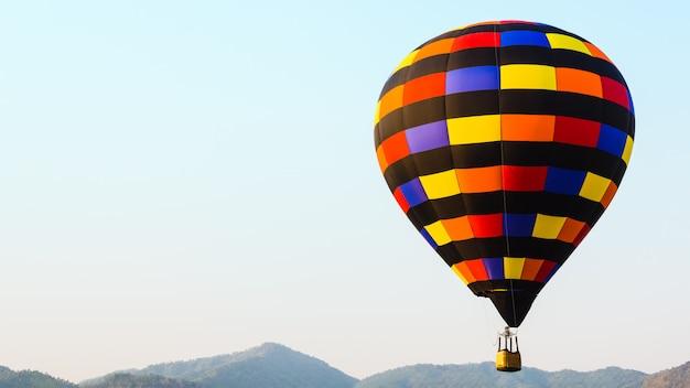 Balão de ar quente colorido com fundo de céu e montanha