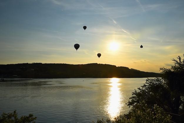 Balão de ar quente colorido está voando ao pôr do sol. represa de brno - república tcheca.
