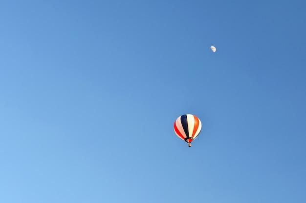 Balão de ar quente colorido que voa no por do sol. fundo colorido natural com o céu.