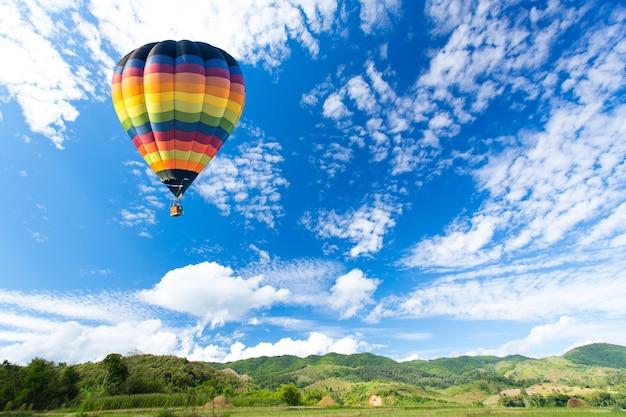 Balão de ar quente colorido sobre campo verde