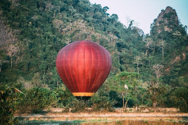 Balão de ar quente colorido subindo bem a tempo de explorar o belo pôr do sol sobre vang vieng, no laos, sudeste da ásia.