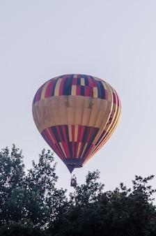 Balão de ar quente está voando ao nascer do sol