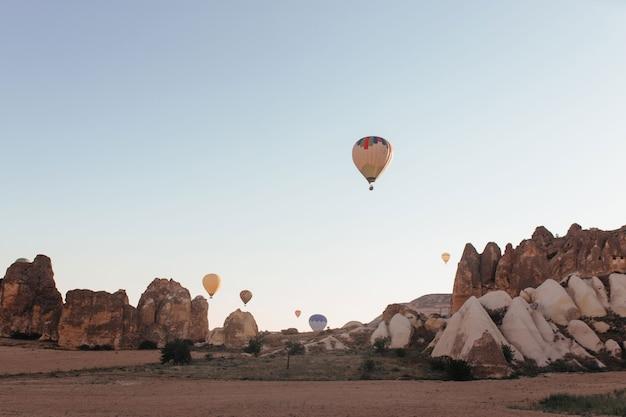 Balão de ar quente pairando sobre as montanhas da capadócia
